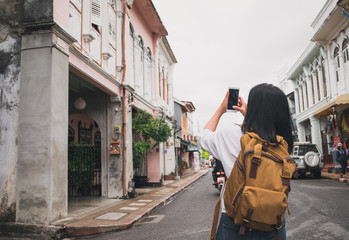 Traveler backpacker use mobile phone taking photo of old town city while traveling.sightseeing at city.