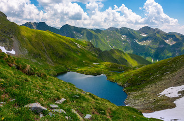 Beautiful landscape in Fagarasan mountains. Popular travel destination. Capra lake between hills, mountain ridge in the distance on a cloudy summer day