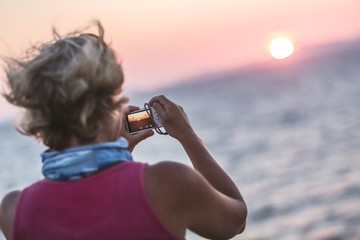 Woman taking a picture with camera on the yacht. Beautiful summer day at the Adriatic coast, Croatia. Sunset and sea horizon in the background.