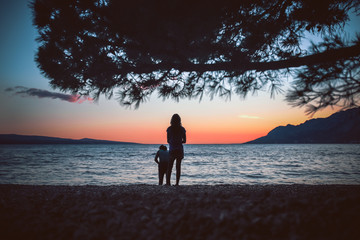 Family summer vacation in Croatia. Mom and daughter on the pebble beach enjoying the beautiful sunset.