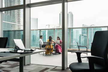 Three Indian employees during break on the terrace of a modern business building
