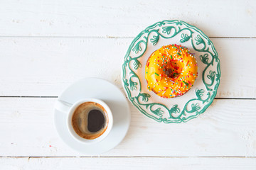 Yellow donut and coffee on wood background. Top view