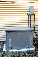 Residential generator on concrete pad, next to a house wall
