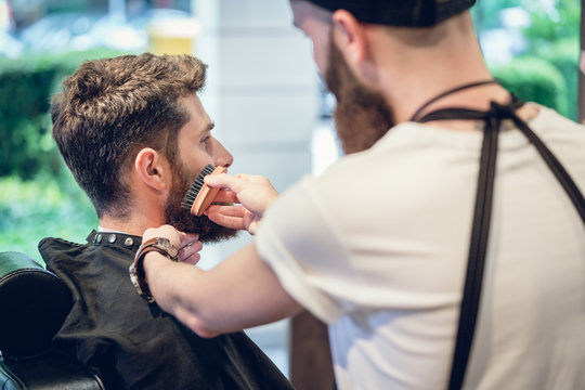 Close-up of the hands of a skilled barber using a handless brush with boar bristles, while grooming the beard of his young customer in a trendy hair salon for men only