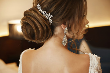 Wedding hairstyle - fashionable brown-haired young woman, in a lace dress and with earrings