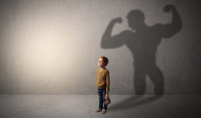 Muscleman shadow behind waggish little boy