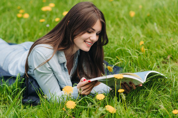 Woman reading on grass in park
