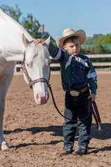 cute, small boy in cowboy outfit standing with large white horse