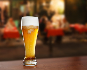 cold glass with beer on the background of a outside bar.