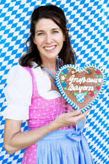 bavarian woman in dirndl holding a heart-shaped gingerbread