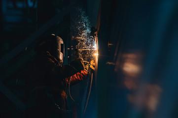 Man welder at work sparks wall metal welding