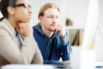 Young office worker sitting at meeting with his colleague