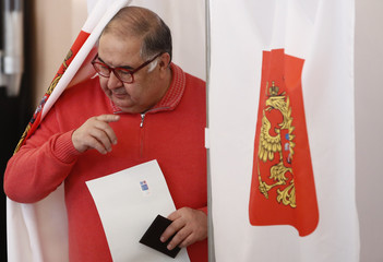Russian billionaire Usmanov walks out of a voting booth at a polling station during the presidential election in Moscow