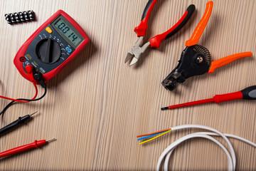 Digital clamp meter electric tester multimeter and electrick set on woodden background.