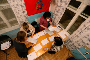 Members of a local election commission sort ballots before starting to count votes during the presidential election at a polling station in the Siberian village of Verkhniaya Biryusa