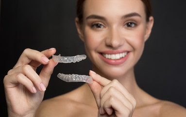 Taking care of teeth. Close up of clear aligners in hands of happy girl who is standing and showing orthodontic device to the camera. Selective focus and isolated background