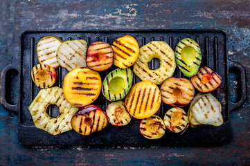 GRILLED FRUITS. Grill fruits - pineapple, peaches, plums, avocado, pear on black cast iron grill board Wall mural