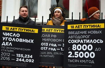 Anti-Putin protesters hold placards outside the Russian Embassy in London