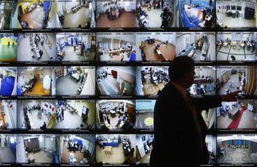 A man stands in front of a screen showing a live broadcast from polling stations during the presidential election, at the headquarters of Russia's Central Election Commission in Moscow