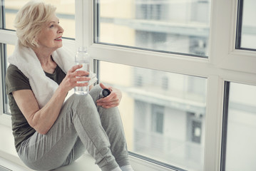 Good looking old woman sitting on windowsill with bottle in hand, she is looking out the window with smile. Copy space in right side
