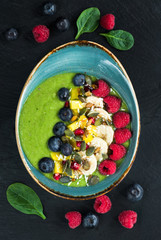 Green avocado, spinach and grape smoothie garnished with fresh fruit