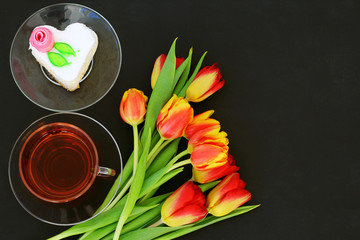 bouquet of tulips on the table with a Cup of tea and cake in the form of a heart