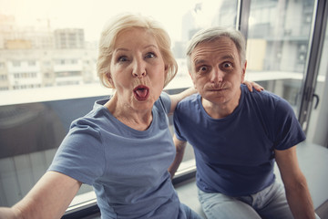 Portrait of joking elderly people playing the ape while making selfie near window indoors