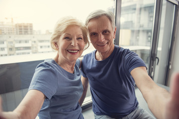 Waist up portrait of contented mature man and woman hugging and taking photo of themselves on windowsill