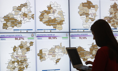 A woman stands in front of a screen showing a voter turnout in regions of the country during the presidential election, at the headquarters of Russia's Central Election Commission in Moscow