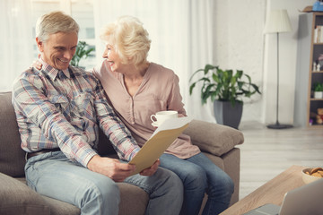 Old man resting on couch and looking at documents with satisfaction. His glad wife sitting with cup and hugging him Wall mural