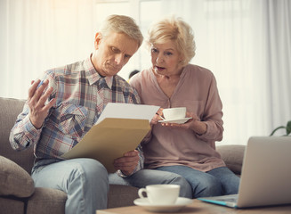 Portrait of calm mature couple concentrated on record in male hand while resting at home with comfort