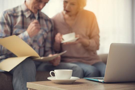 Focus on mug and laptop on table. Elderly couple focused on documents on background
