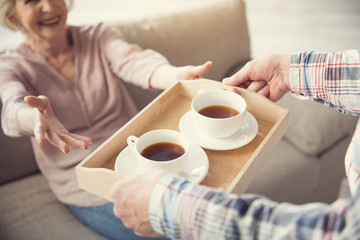 Old male hands giving tray with cups of tea to enjoyed senior female person. Focus on salver. Close up