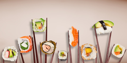 Traditional japanese sushi pieces placed between chopsticks on pastel color background.