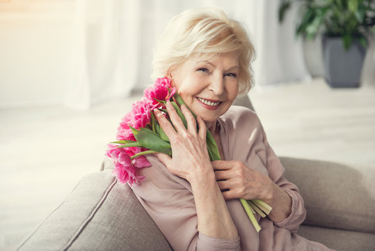 Portrait of old woman relaxing on cozy sofa with bunch of flowers in hug. She is looking at camera with happiness