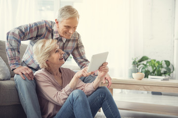 Happy old woman sitting on the floor and pointing at tablet to her husband. Glad man is resting on couch. Copy space in right side