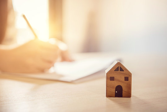 Close up wooden toy house with Woman signs a purchase contract or mortgage for a home, Real estate concept.