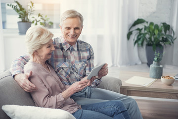 Delighted mature man and woman relaxing on divan at home with tablet. Copy space in right side