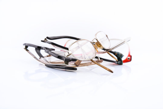 Group of old broken eyeglasses on white background. Move for create place for text. Concept - update your old accessory