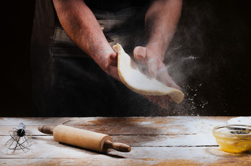 Cooking Italian national food with chef and ingredients for pizza. Dough in chef hand on a dark black background of wood. Baking bread, pizza, pasta. Recipe from chef cooks pizza.