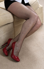 Woman wearing fishnet tights and red high heel shoes
