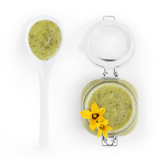 zucchini green sauce in jar with flowers and spoon food top view, isolated on white
