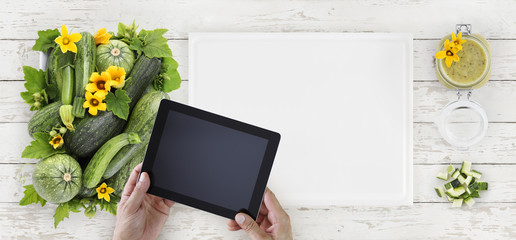 zucchini, flowers and green sauce food top view, hands with digital tablet on white cutting board in kitchen wooden worktop