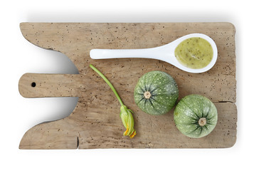 zucchini on wooden cutting board, flower and spoon of sauce food top view isolated on white background