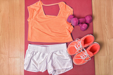 Gym fitness clothing on floor for strength training workout at home top view. Orange matching t-shirt and running shoes, white shorts, pink girly dumbbells weights on mat.
