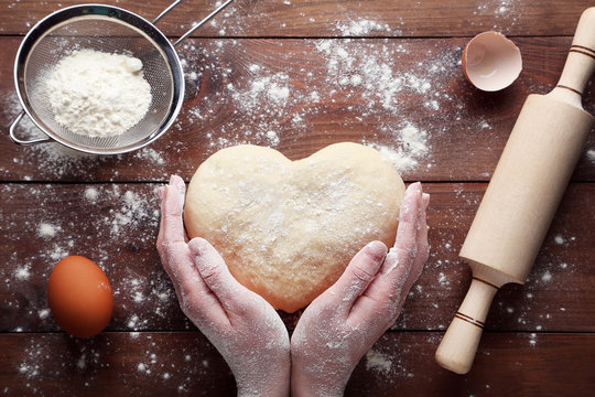 Female hands holding raw dough in heart shape on wooden table