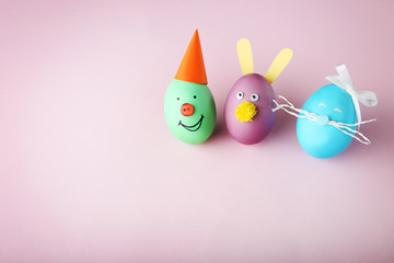 Eggs with funny faces on pink background