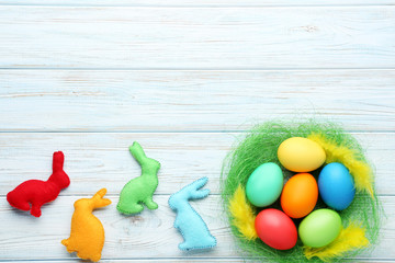 Colorful easter eggs in green nest with fabric rabbits on wooden table
