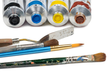Set of oil paint tubes and painting tools on a white surface