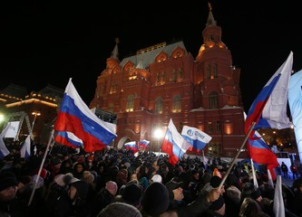 People wave Russian flags during a rally and concert marking the fourth anniversary of Russia's annexation of the Crimea region, at Manezhnaya Square in central Moscow